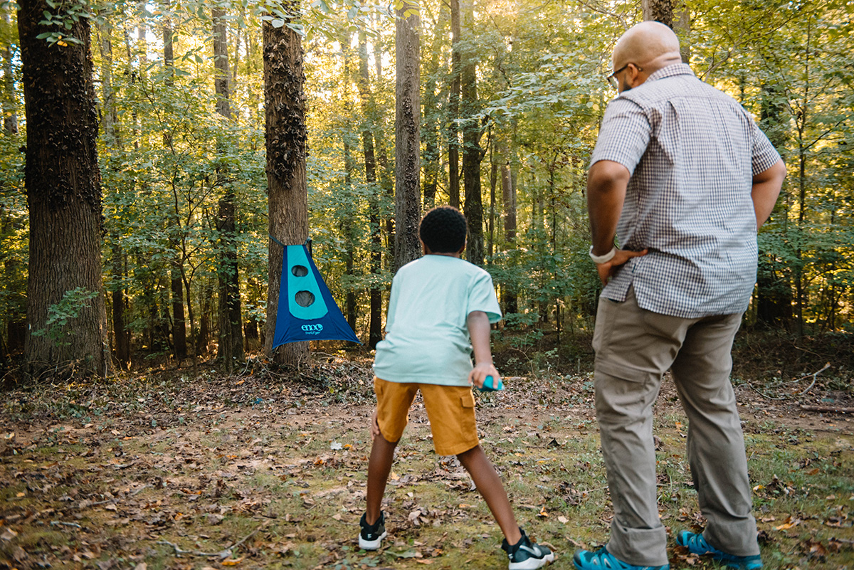 A man and his son play TrailfFyer in the woods.