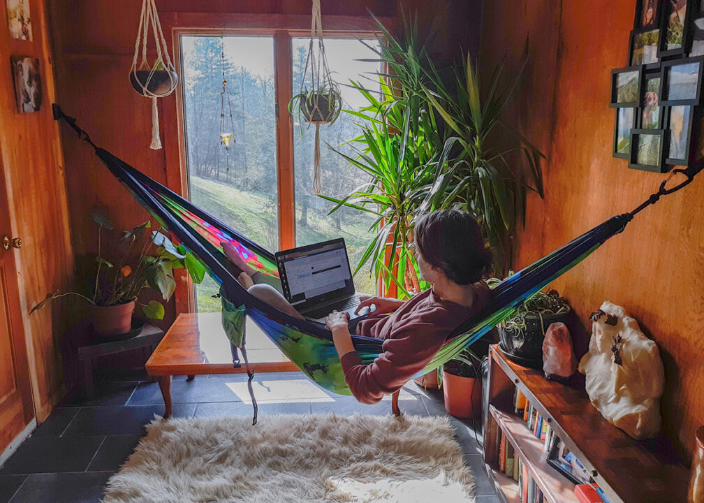 A woman sits in her Tie Dye Hammock inside her house using the Deluxe Indoor Hammock Hanging Kit.