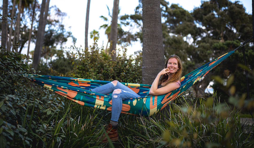 A woman lies in a colorful DoubleNest Print Hammock in the Lagoon print.