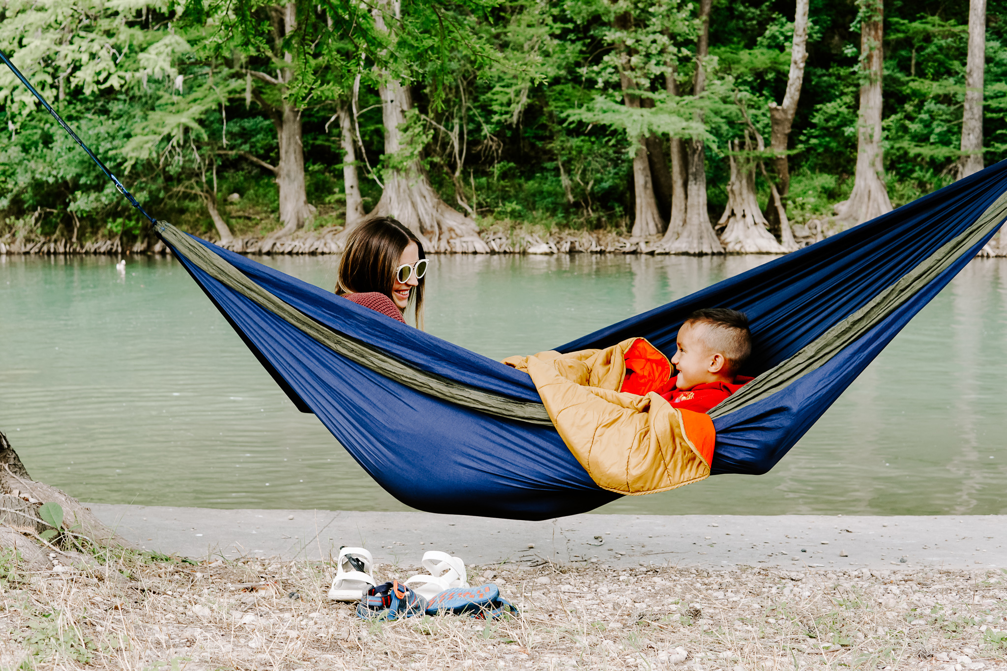 A woman and her son share a DoubleNest hammock by the water.