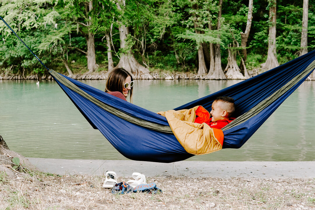 Mom and son in DoubleNest hammock outside by lake.