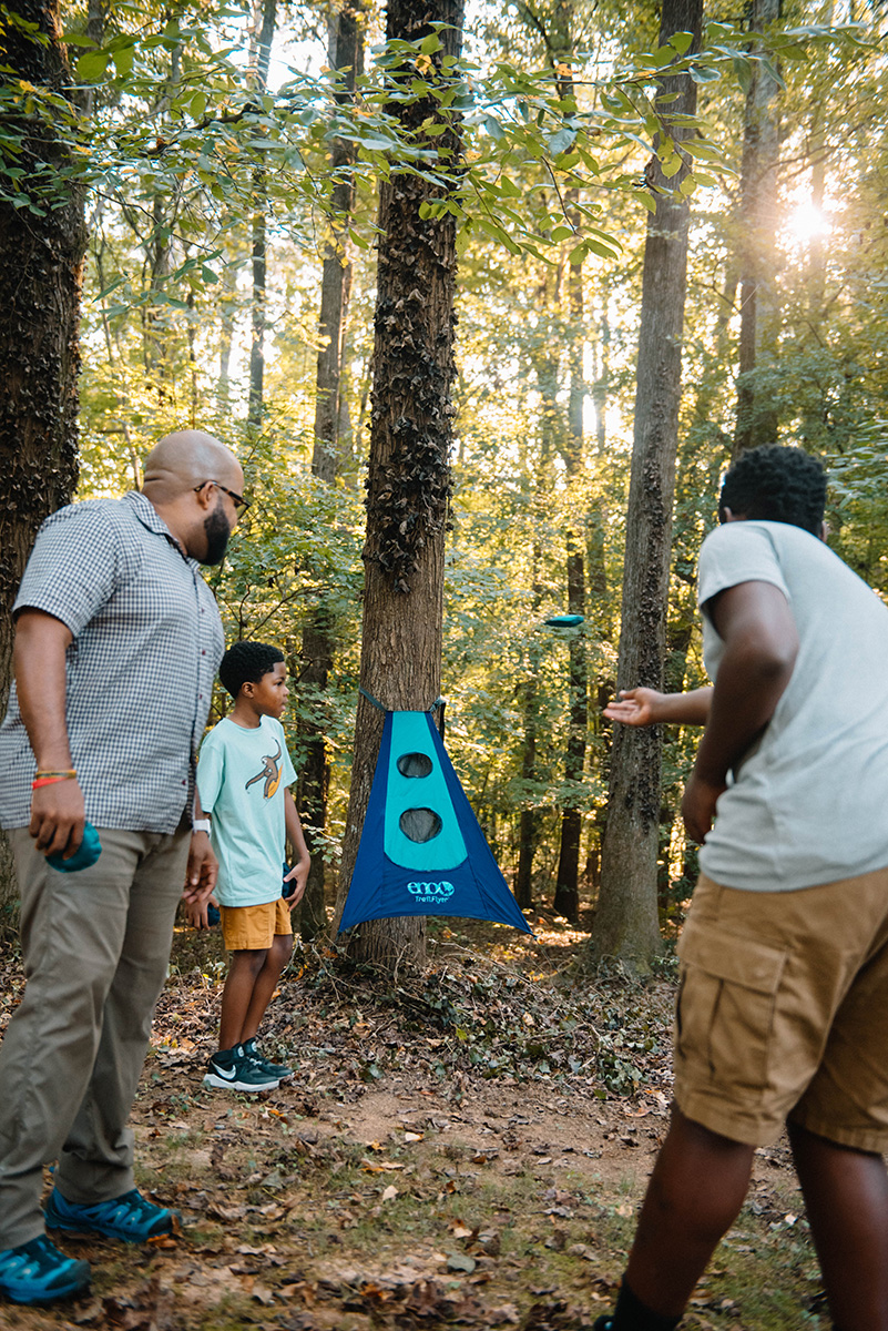 A man and his two sons playing TrailFlyer in the woods.