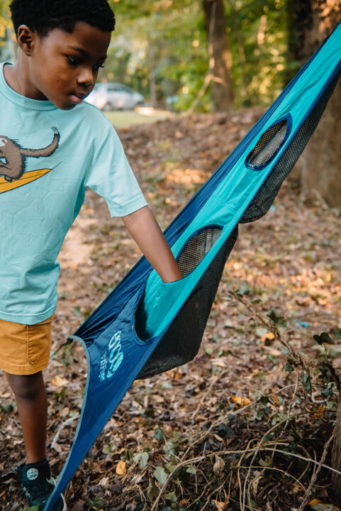 A boy reaches into the pocket of a TrailFlyer to retrieve a disc.
