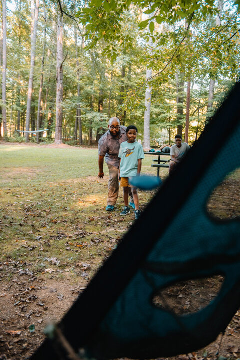 A man and son toss discs while playing ENO's TrailFlyer outdoor game.
