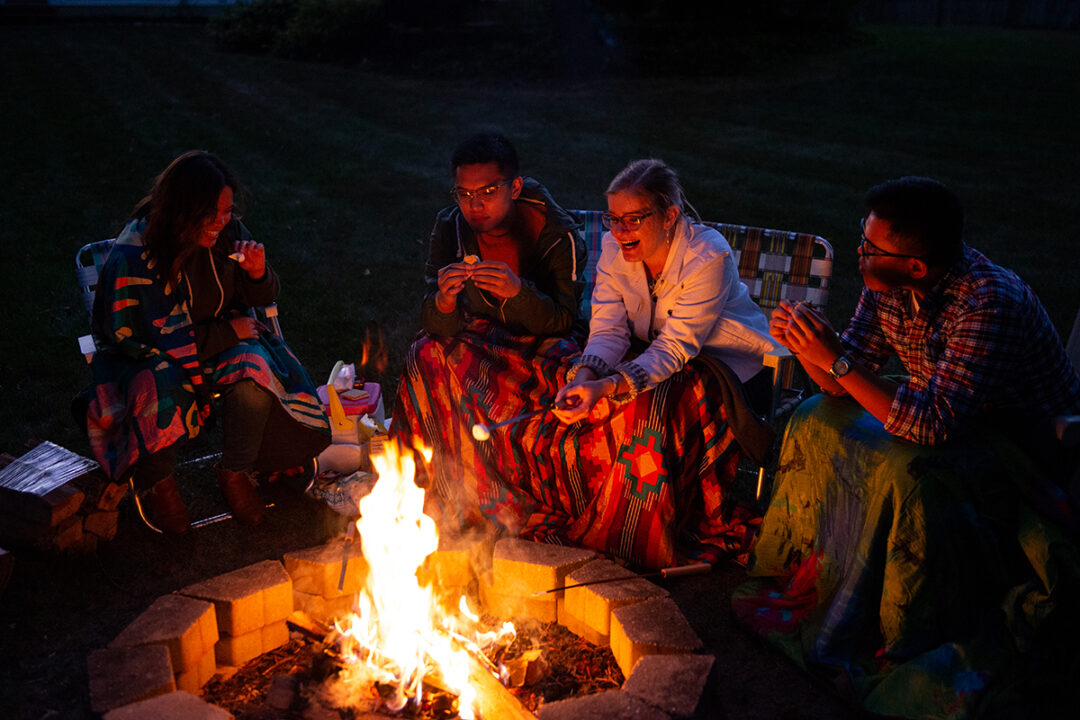 A group of four people using FieldDay Blankets roasting marshmallows by fire.