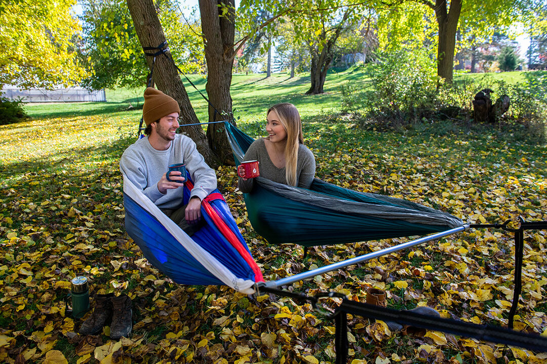 A man and woman drink coffee in side-by-side DoubleNest hammocks while using the Fuse Tandem Hammock System