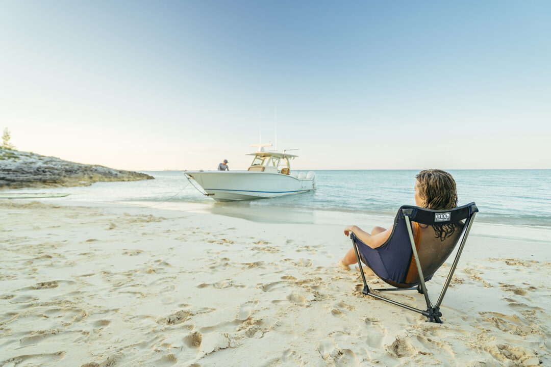 A woman sits in a Lounger SL chair on the beach near a docked boat.