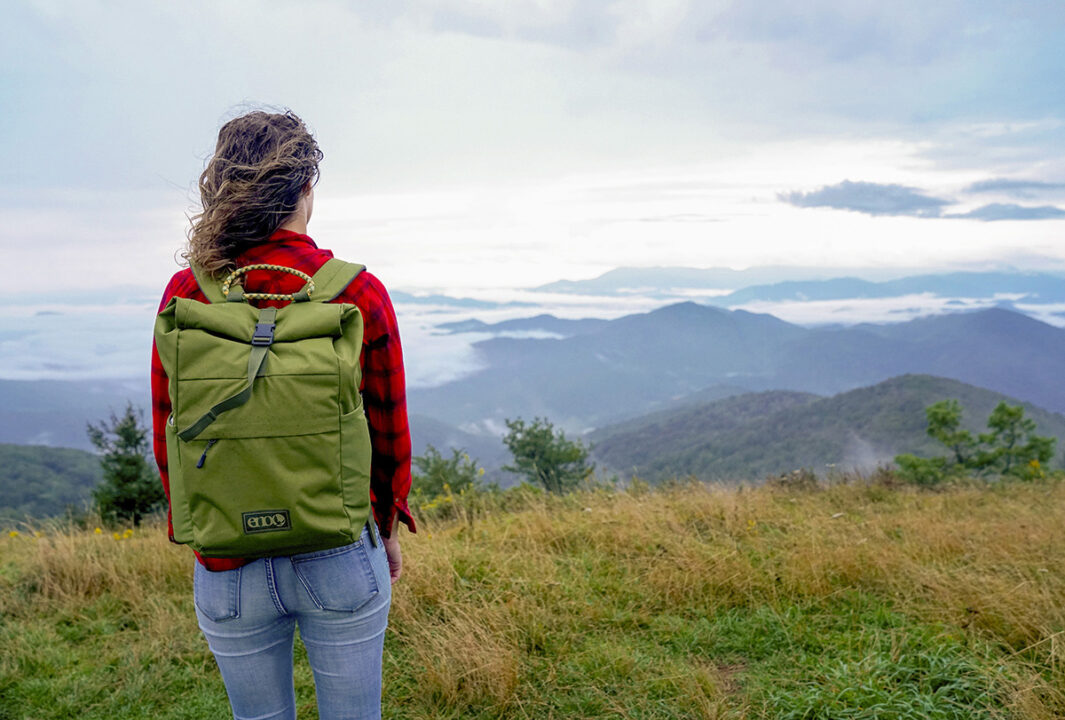 Woman on top of mountain using Roan Rolltop Pack.