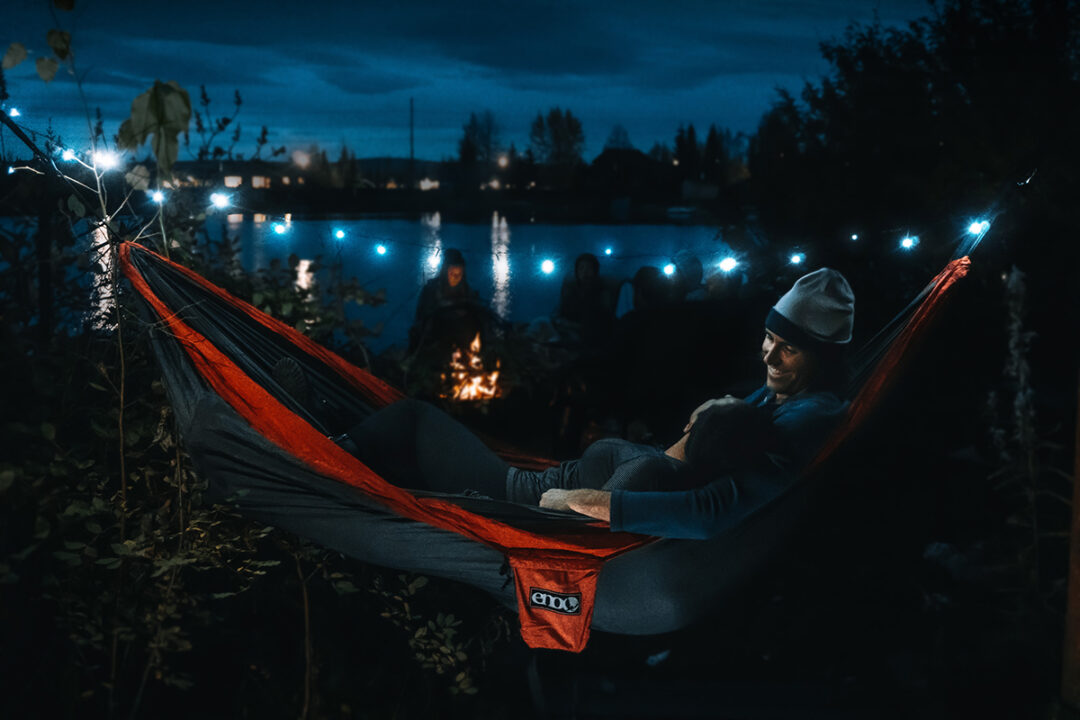Man and woman sharing DoubleNest at night using Twilights Camp Lights.