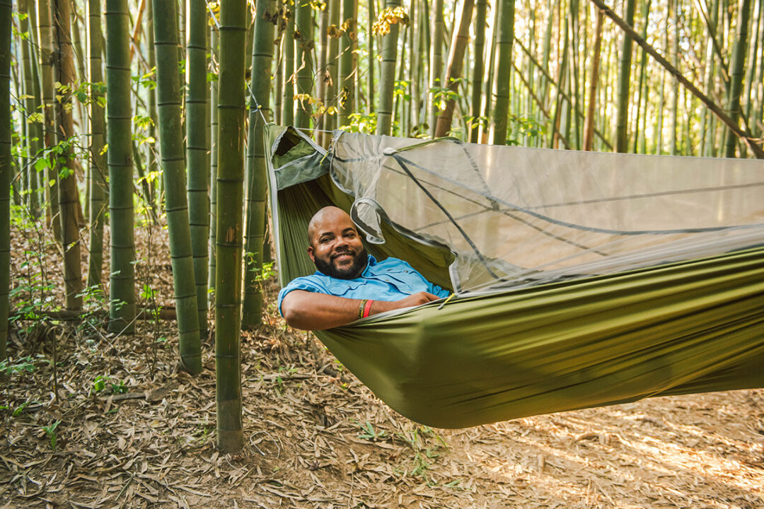Man laying in green JungleNest hammock in a bamboo forest.