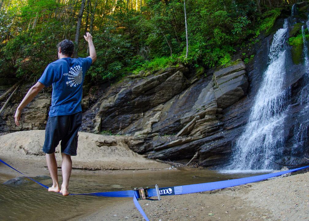 A man walks on the Slackwire Slackline near a waterfall