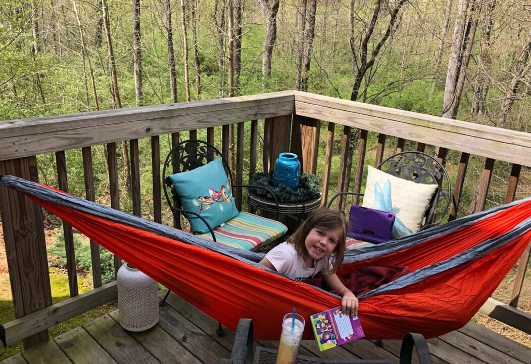 A young girl reads while sitting in her hammock on her porch.