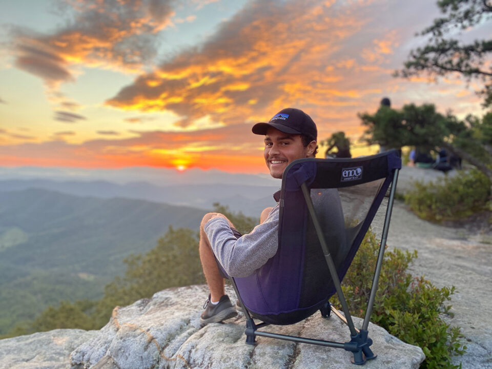 A man sits in a Lounger SL chair on the top of a mountain, surrounded by beautiful views.