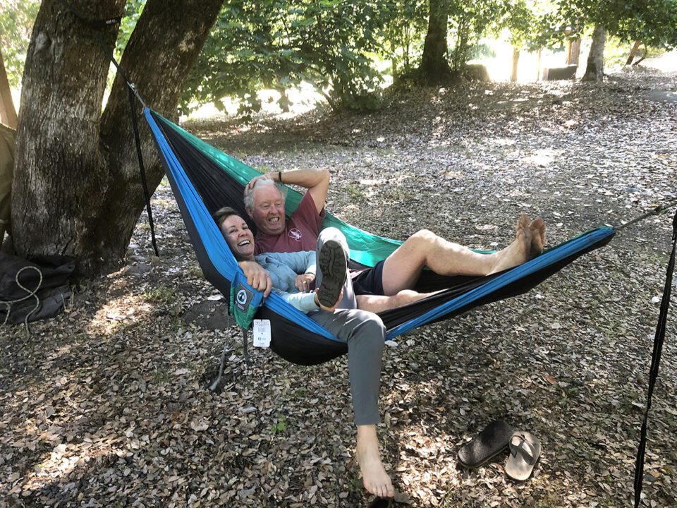 A man and a woman share a PCT Giving back hammock.