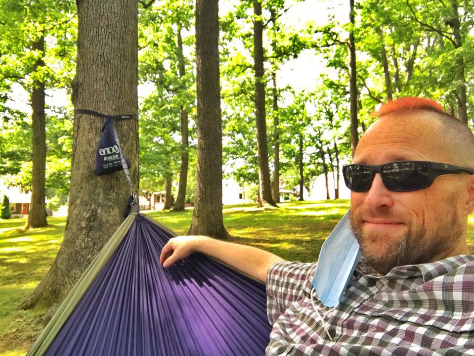 A man hangs in a hammock in a park.