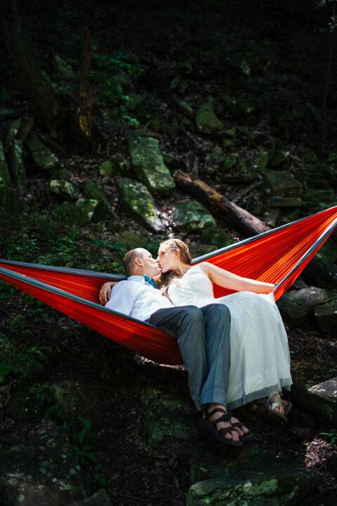 A man and woman, wearing wedding attire, kiss in an orange hammock.