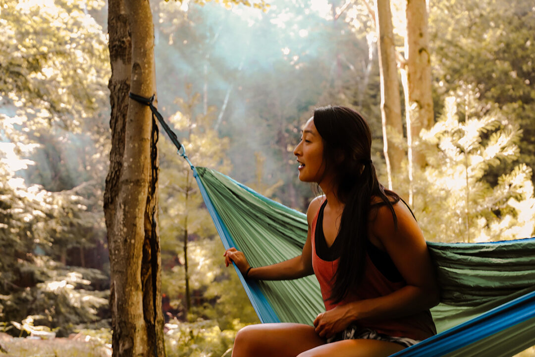 A woman sits in a green and blue hammock in the middle of the woods.