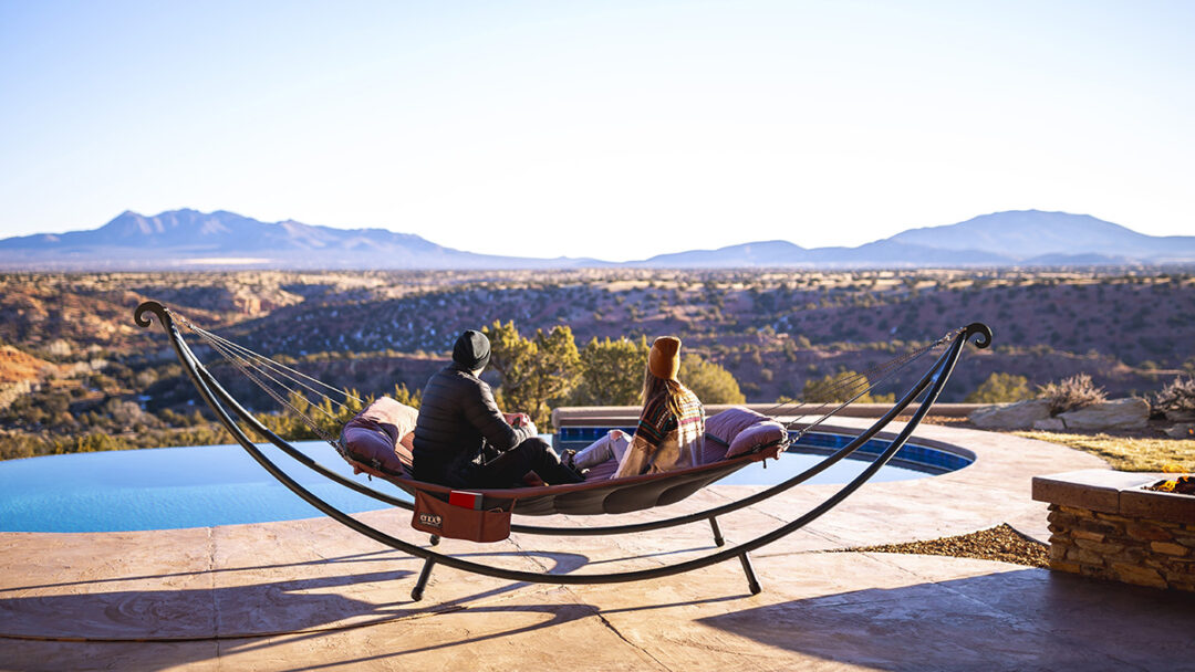 A man and a woman sit in the SuperNest Hammock in the SoloPod XL Hammock Stand while soaking in the mountains of New Mexico.