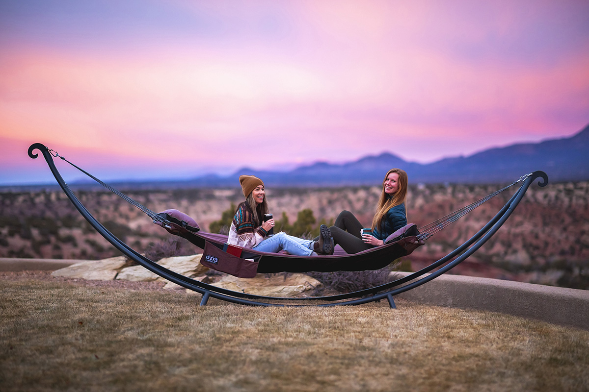 Two women sit in the SuperNest hammock during sunset in New Mexico.
