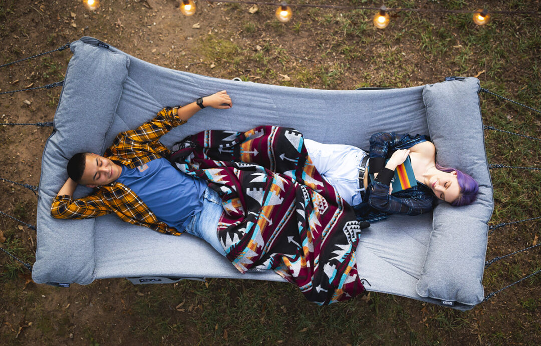 An aerial view of a man and a woman laying on opposite sides of the SuperNest Hammock in their backyard.