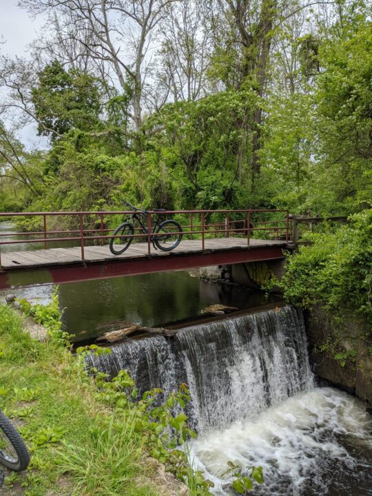 Mountain bike sits centered on a small bridge over a canal waterfall surrounded by greenery.