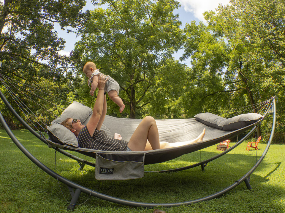 A woman raises her baby into the air as she lays on the SuperNest Hammock in the SoloPod XL Hammock Stand in her backyard.