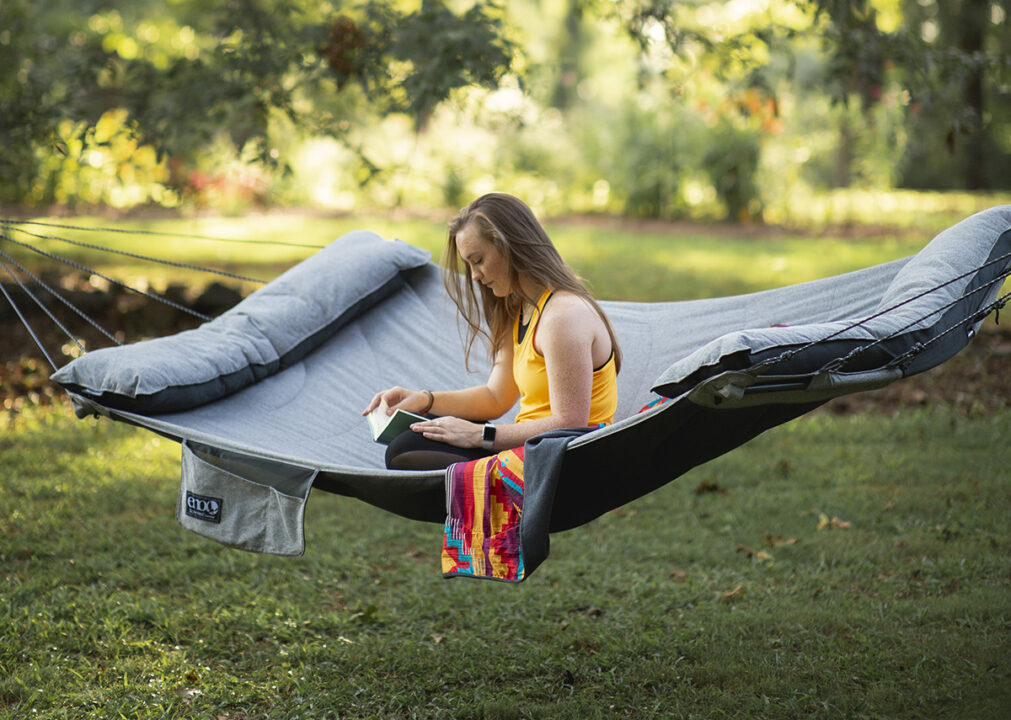 A woman reads while sitting in the SuperNest Hammock.