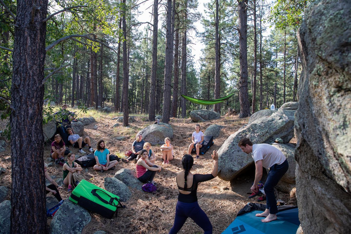 Students in athletic gear sit, watching as instructor shows bouldering techniques in the woods. There is a hammock in the background.