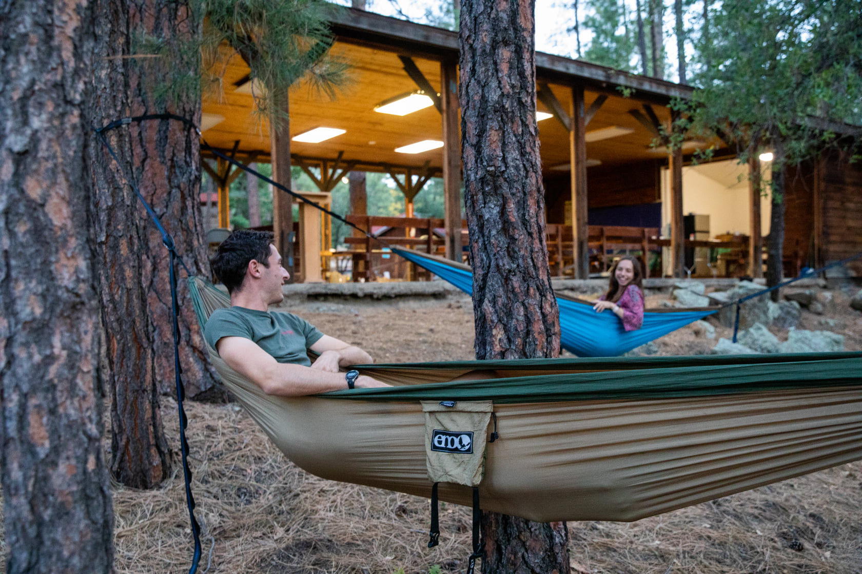 Students laying in ENO hammocks, outside of an open air building at A Place Beyond located in Prescott National Forest.