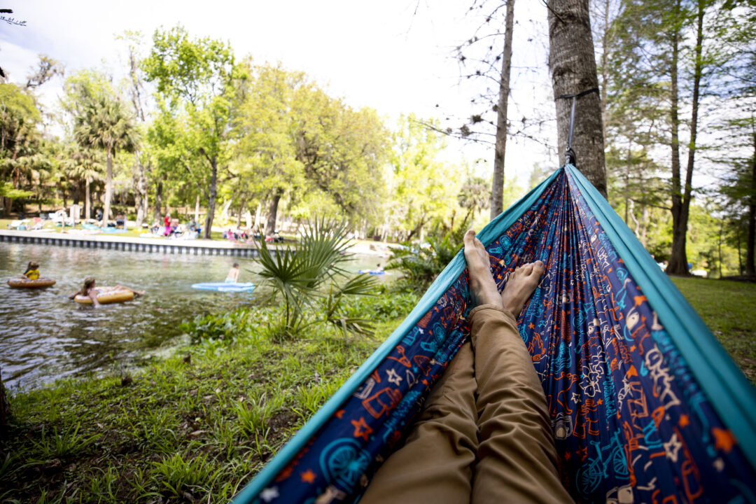 A man lays in an ENO hammock as people tube down Rock Springs at Kelly Park in Florida