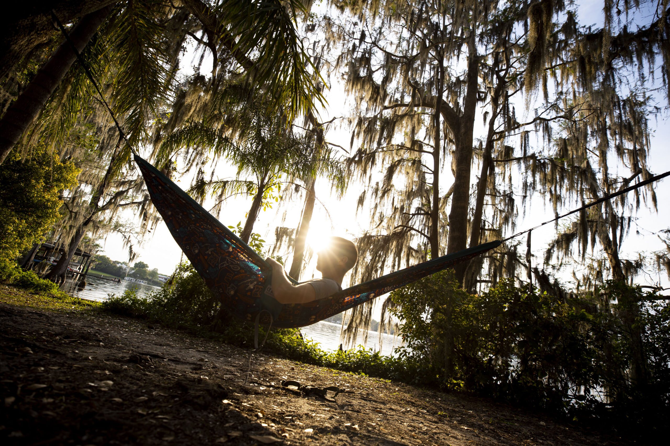 A man lays in a hammock surrounded by Spanish Moss in Azalea Garden in Winter Park, Florida.