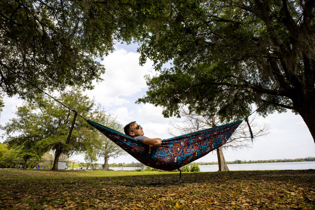 A man relaxes in his hammock with a lake and dog park in the background nearby.