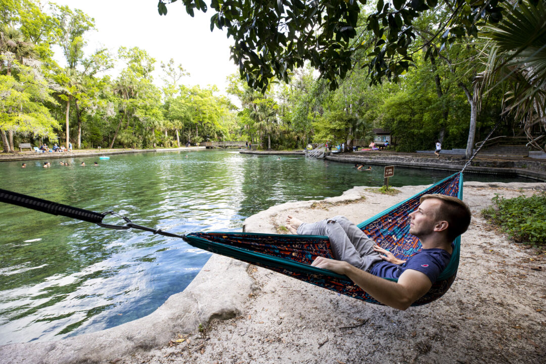 A man lays in an ENO hammock on the edge of Wekiwa Springs State Park.