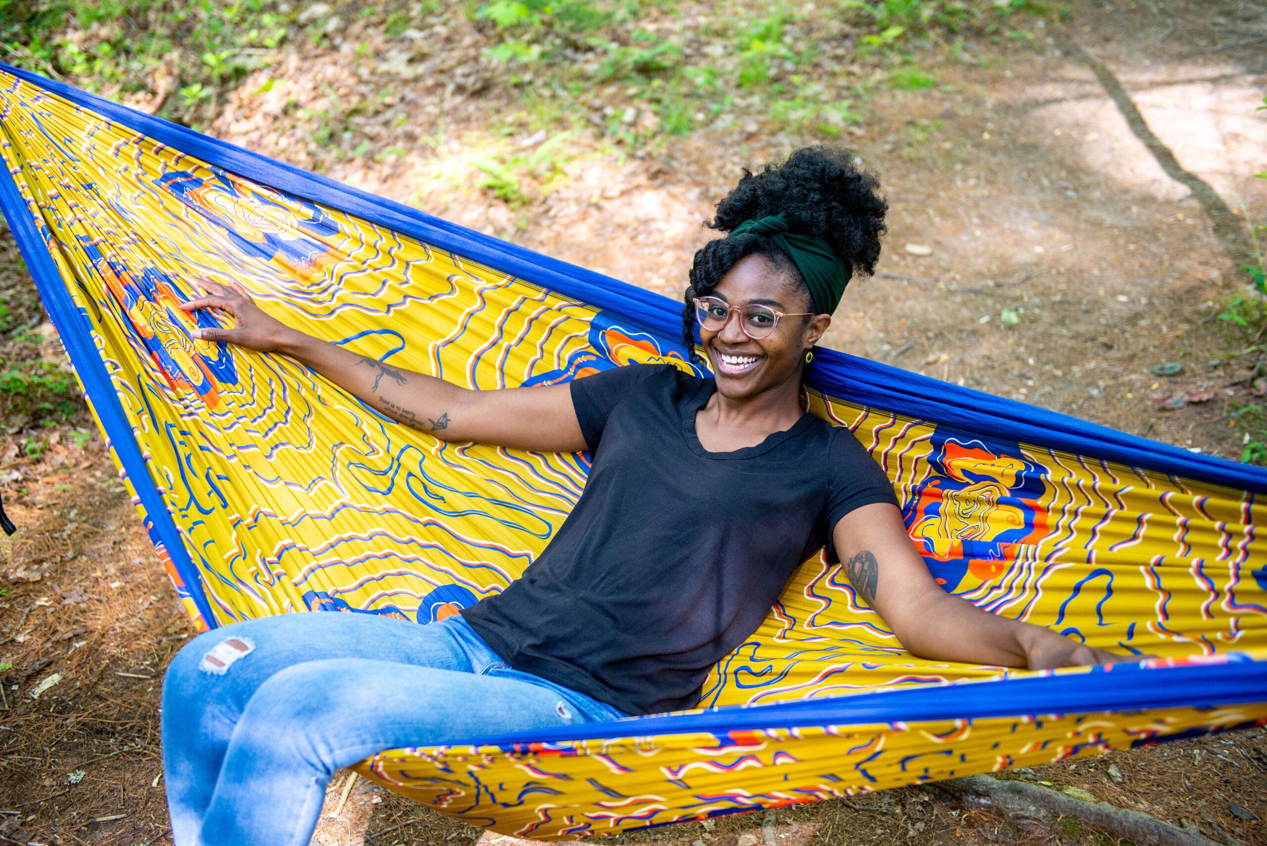 Leandra Taylor, the artist and Outdoor Afro volunteer leader lounging in the Kili Mapp Kili DoubleNest Hammock Print she designed.